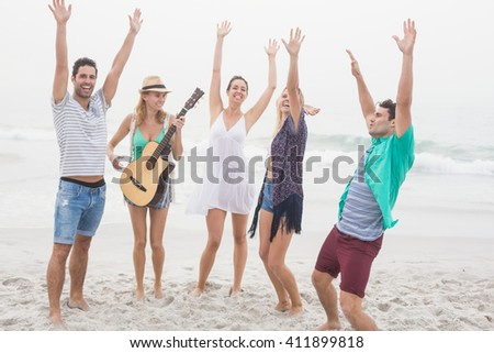 Group of friends playing guitar and dancing on the beach