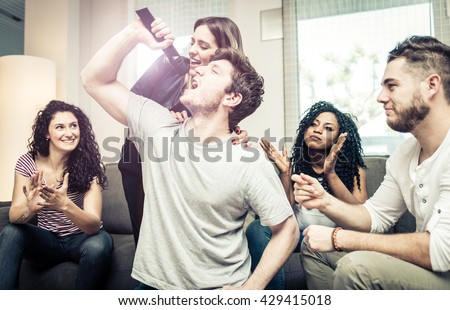 Group of friends playing hard with video games and karaoke. Having fun at home - stock photo