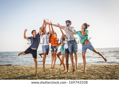Group of Friends Playing with Ball at Beach - stock photo