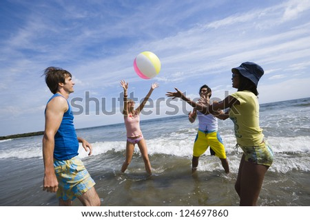Group of friends playing with ball in water