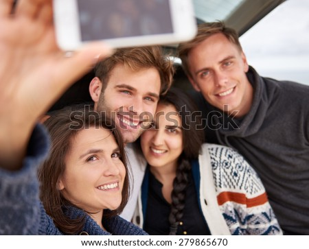 Group of friends posing for a selfie together while on a roadtrip - stock photo