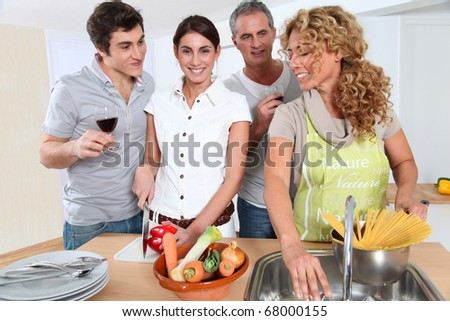 Group of friends preparing dinner in home kitchen - stock photo