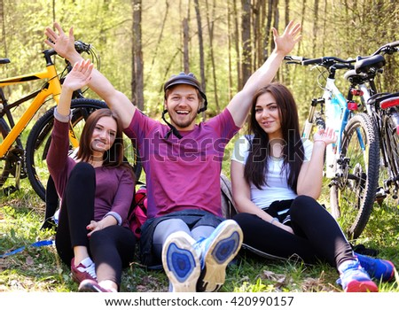 Group of friends relaxing in a park after bicycle riding.