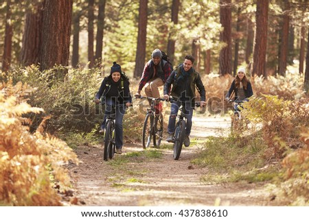 Group of friends riding bikes on a forest path, front view - stock photo