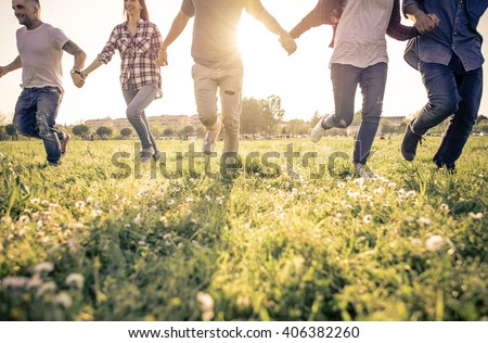 Group of friends running happily together in the grass - stock photo