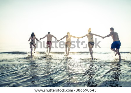 Group of friends running on the beach at sunset - Summer vacation on a tropical beach