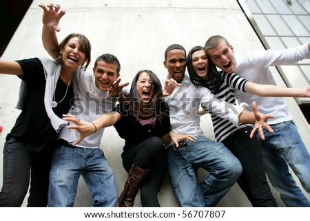 Group of friends screaming with arms up - stock photo