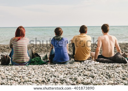 Group of friends sit near the sea. Photo from the back.