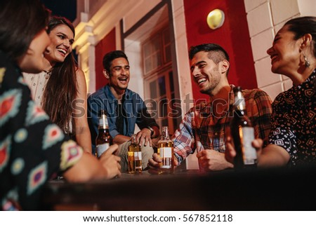 Group of friends sitting around a table at rooftop party with beers. Young people on rooftop with drinks.