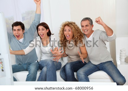 Group of friends sitting in sofa watching sport game on tv