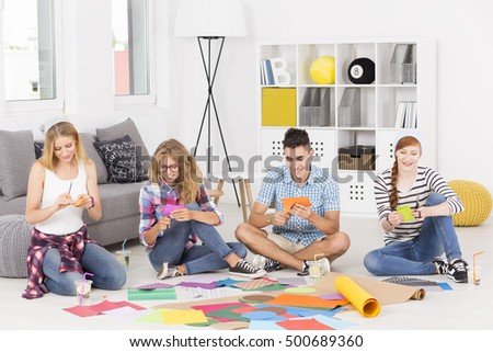 Group of friends sitting on the floor and making a paper cutouts