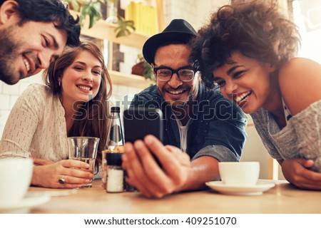 Group of friends sitting together in a cafe looking at mobile phone and smiling. Young guy showing something to his friends on his smart phone. - stock photo