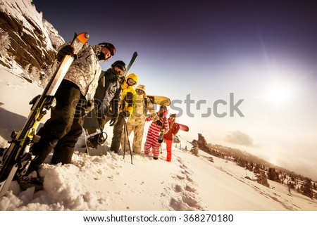 Group of friends skiers and snowboarders standing on the slope on background of valley. Sheregesh resort, Siberia, Russia - stock photo