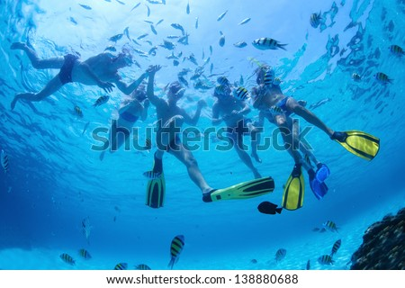 Group of friends snorkeling and feeding fish in a sea - stock photo