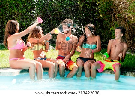group of friends spending time together at the pool - stock photo