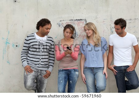 Group of friends standing against wall