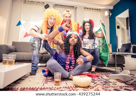 Group of friends supporting their teams - Football fans watching a sport event on television - stock photo