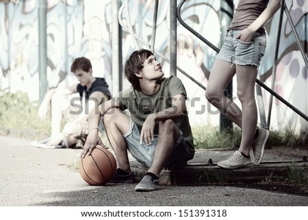 Group of friends taking a break after playing basketball - stock photo