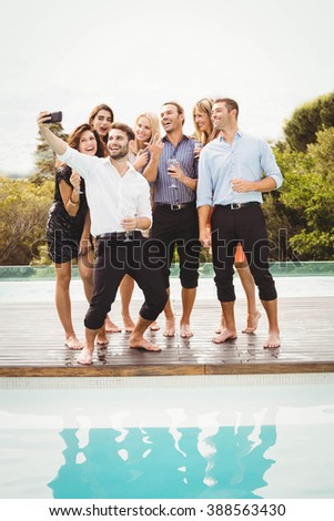Group of friends taking a selfie near the swimming pool in a resort - stock photo