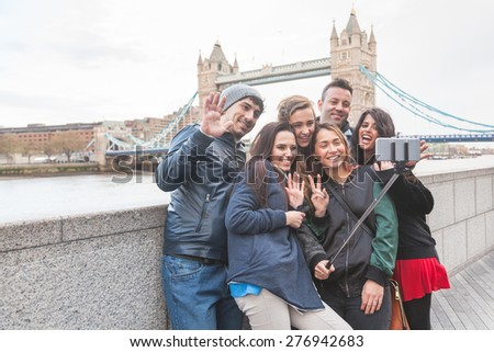 Group of friends taking a selfie using a selfie stick in London with Tower Bridge on background. They are four girls and two boys in their twenties, embracing and having fun together.
