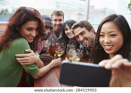 Group Of Friends Taking Photograph At Outdoor Rooftop Bar