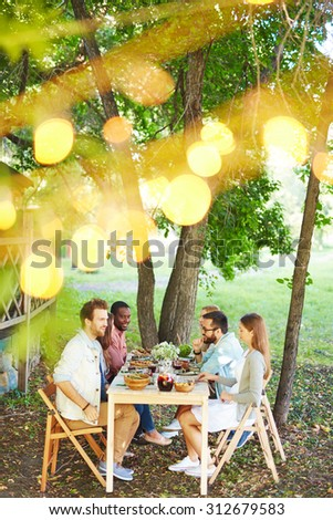 Group of friends talking by Thanksgiving dinner outdoors