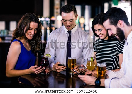 Group of friends texting and having a drink in a bar
