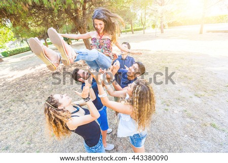 Group of friends throwing a woman in the air. They are six persons with mixed races and ethnies. Friendship, lifestyle and success concepts.