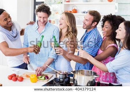 Group of friends toasting beer and wine glasses in kitchen at home - stock photo