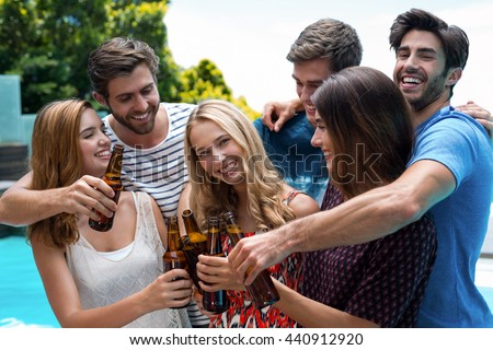 Group of friends toasting beer bottles while enjoying near pool