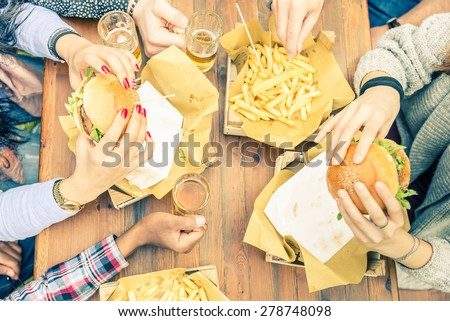 Group of friends toasting beer glasses and eating at fast food - Happy people partying and eating in home garden - Young active adults in a picnic area with burgers and drinks - stock photo