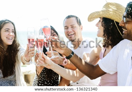 Group of friends toasting champagne sparkling wine at a relax party celebration gathering by the sunny beach - stock photo