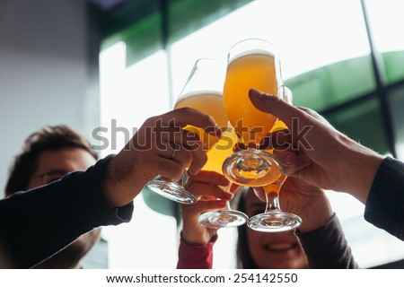 Group Of Friends Toasting In Tavern - stock photo