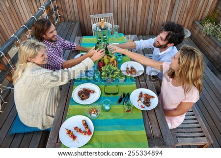 Group of friends toasting to a celebration with drinks while hanging out at a restaurant outdoors - stock photo