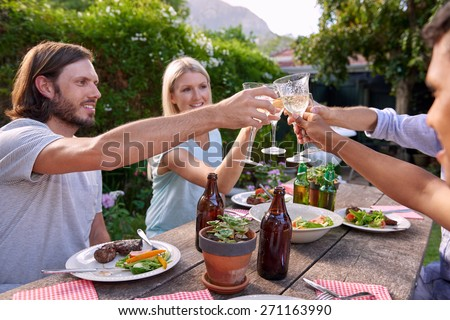 Group of friends toasting to celebration with drinks at garden outdoors party - stock photo