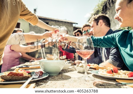 Group of friends toasting wine glasses and having fun outdoors - People having lunch in a restaurant - stock photo