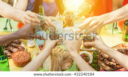Group of friends toasting with aperitif eating barbecue outdoor - Closeup of hands cheering with cocktails and beers - Friendship,summer,fun and dinner concept - Warm filtered look - stock photo