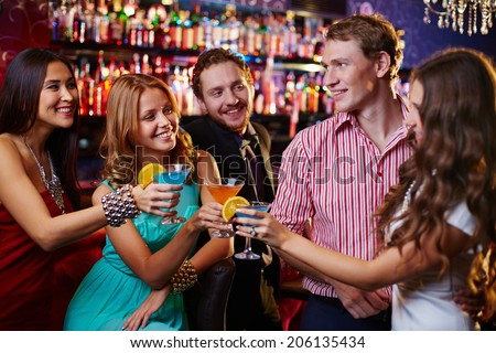 Group of friends toasting with cocktails in the bar - stock photo