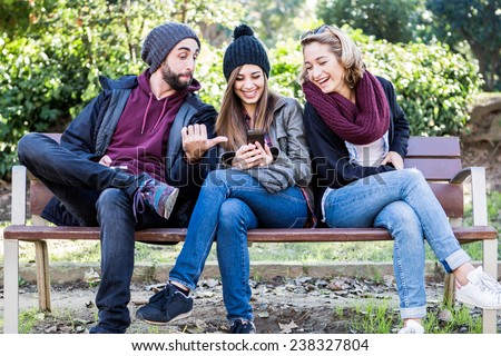 Group of friends two women and one man, sitting on a bench in park