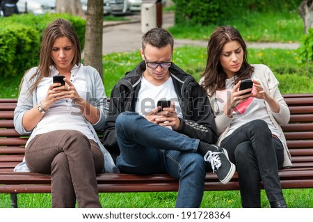 Group of friends two women and one man, sitting on a bench in park separately looking at their phones loosing communication. people using their phones and sending texts as they stand beside each other - stock photo