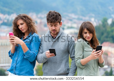 Group of friends two women and one man using smartphone - friendship, technology concept. Three friends holding smart phones and chatting. - stock photo