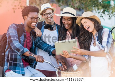 Group of friends using digital tablet and having fun - stock photo
