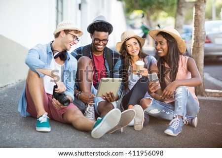 Group of friends using digital tablet and mobile phone on roadside - stock photo