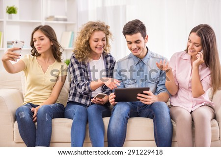 Group of friends using their phones and having fun together. - stock photo