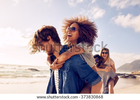 Group of friends walking along the beach, with men giving piggyback ride to girlfriends. Happy young friends enjoying a day at beach. - stock photo