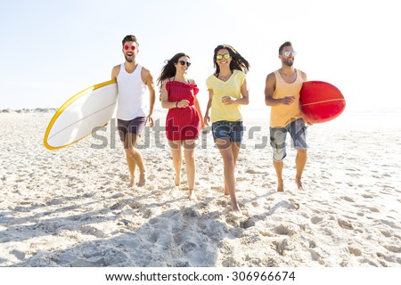 Group of friends walking together at the beach and holding surfboards - stock photo