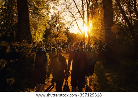 Group of friends walking with backpacks in sunset from back. Adventure, travel, tourism, hike and people friendship concept - stock photo