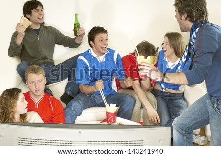 Group of friends watching television and celebrating in living room - stock photo