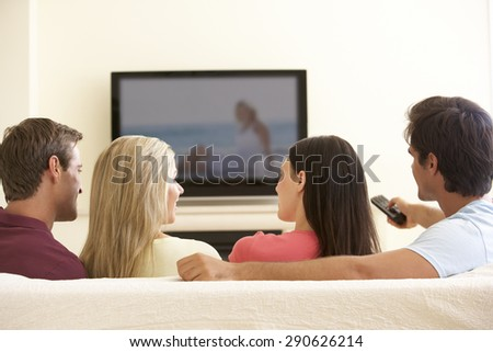 Group Of Friends Watching Widescreen TV At Home - stock photo
