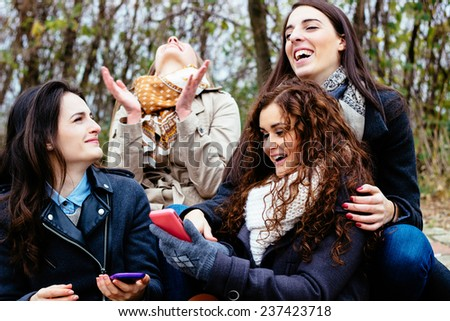 Group of friends with a smartphone, talking and laughing  - stock photo